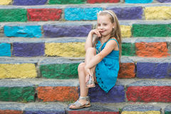 Small smiling baby girl in blue dress on colorful stairs Stock Images