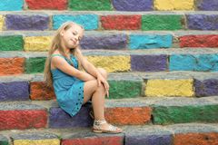Small smiling baby girl in blue dress on colorful stairs. Small baby girl or cute child with adorable smiling face and bow in blonde hair in blue dress outdoor stock images