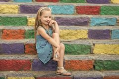 Small smiling baby girl in blue dress on colorful stairs. Small baby girl or cute child with adorable smiling face and bow in blonde hair in blue dress outdoor stock photo