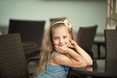 Small smiling baby girl in blue dress near cafe table. Small baby girl or cute happy child with adorable smiling face and bow in blonde hair in blue dress stock images