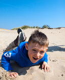 Small smiling boy lying in sand Royalty Free Stock Image