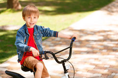 Small smiling boy riding bike Royalty Free Stock Photography