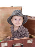 Small smiling boy sits in an open road suitcase. Royalty Free Stock Photo