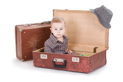 The small smiling boy sits in an open road suitcase. Stock Image