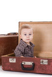 The small smiling boy sits in an open road suitcase. Royalty Free Stock Images