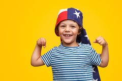 Excited boy with flag on head showing biceps. Small smiling boy in striped t-shirt and with American flag on head demonstrating biceps on yellow backdrop stock image