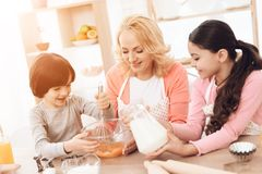 Small smiling boy is whipping eggs in bowl with his sister and young grandmother. Happy little girl pours milk into bowl with eggs Royalty Free Stock Photos