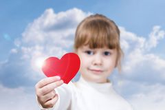 A kid is holding a heart in her hand stock images