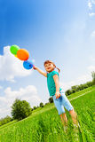 Small smiling girl with colorful balloons Stock Photos