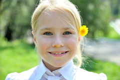 Small smiling girl with a dandelion portrait. Beautiful blonde smiling girl with a dandelion behinde ear portrait Royalty Free Stock Image