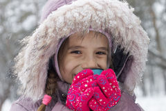 Small smiling girl drink hot tea in winter park Royalty Free Stock Photography