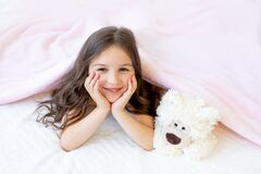 A small smiling girl 5-6 years old is lying in bed with a Teddy bear, hands under her cheeks