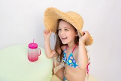 A small smiling girl of 5-6 years old is sitting in a swimsuit and a hat with a cocktail on a white isolated background, a place