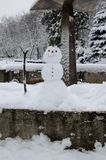 Small smiling snowman in city park Stock Photos