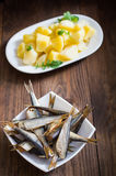 Small smoked fish baltic herring with boiled potatoes. Wooden background. Close-up. Top view royalty free stock image