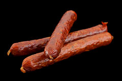 Small smoked sausage on black. Small smoked sausage with spice isolated on black background Stock Photo