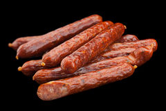 Small smoked sausage on black Stock Photography