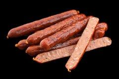 Small smoked sausage on black Stock Photos