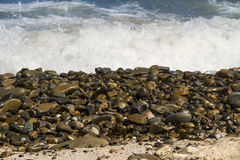 Small smooth rocks on seashore. Thousands of small, smooth, wet rocks on the seashore Stock Photos
