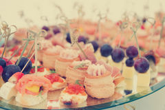 Small snacks on banquet table, toned Stock Photos