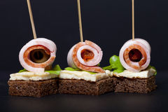 Small snacks canape with brisket, rye bread, omelet and lettuce Royalty Free Stock Image