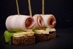 Small snacks canape with brisket, rye bread, omelet and lettuce Stock Photo