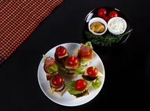 Small snacks canape with cherry tomatoes, cheeze, sausages and vegetables on bread on skewers on white plate with plate of sauces Royalty Free Stock Images