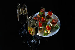 Small snacks canape with cherry tomatoes, cheeze, sausages and vegetables on bread on skewers on white plate with two glasses of c Stock Photos