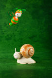 Small snail and bee, green background Stock Photo