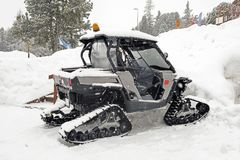 A small snowcat in the parking lot while snowing in alps switzerland.  Stock Images