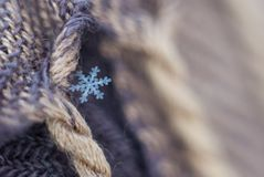 A small snowflake fell on the canvas beige-brown scarf and caught on the fringe as if hiding stock images