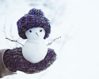Small snowman in a knitted cap on a mitten against the background of snow in the winter. Festive background with a lovely snowman. Stock Photos