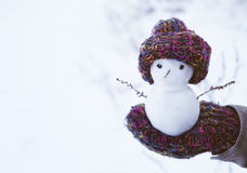 Small snowman in a knitted cap on a mitten against the background of snow in the winter. Festive background with a lovely snowman. Royalty Free Stock Photo