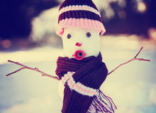Small snowman in snow with a knitted hat and scarf  Stock Images