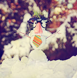 Small snowman in snow with a knitted hat and scarf on Royalty Free Stock Image