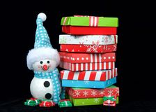 Snowman next to stack of bright christmas presents on black background Stock Photos