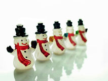 Small snowmen over white. Row of small snowmen over a white background Royalty Free Stock Photos