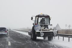 Small snowplow with brushes removing snow. Small snowplow with brushes rides on the route and removing snow Royalty Free Stock Photo