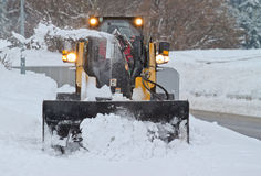 Small snowplow plowing walkway in heavy snowfall Stock Images