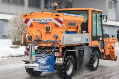 Small snowplow removing snow from street  and sprinkled salt ant Royalty Free Stock Photos