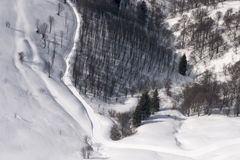 Small snowy road in mountain woods from above, Orobie Royalty Free Stock Photography