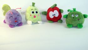 Small soft children`s toys depicting fruits, vegetables and a small fly. The picture was taken in close-up. royalty free stock photos