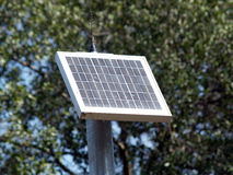 Small solar panel on pole with trees Royalty Free Stock Images