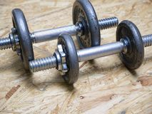 Solid metal dumbbells. Small solid metal dumbbells on white surface background Royalty Free Stock Images