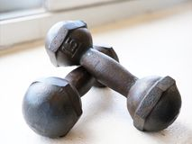 Solid metal dumbbells. Small solid metal dumbbells on white surface background Royalty Free Stock Photos