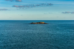 Small solitary island in the ocean. Lonely, solitary green island surrounded by ocean, sea with space for text, copy space Coffs Harbour, Australia Stock Photography