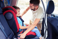 Small son in car seat being put in back of car by father Royalty Free Stock Images