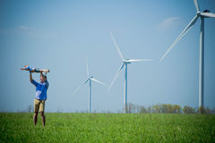 A small son flies in the arms of his father. Near the wind turbines royalty free stock photo
