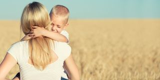 A small son gently hugs his mother in a wheat field. Little son gently hugs his mother in a wheat field royalty free stock photos