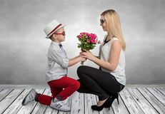 Small son gives his beloved mother a beautiful bouquet of pink roses . Spring, concept of family vacation. Women`s day,mother`s da royalty free stock photo